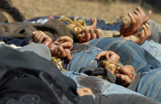 Men with their hands tied behind their backs lie dead in a field near